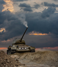 A War Scene Of A Tank Climbing Up The Hill With A Smoking Turret Under A Dramatic Sunset