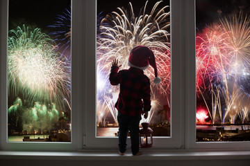 Toddler child standing in front of a big french doors, leaning against it looking at new years eve fireworks