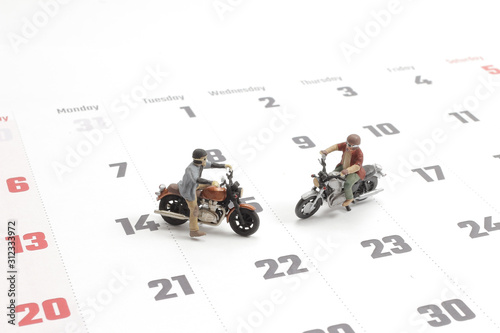 Photo Close up of two traveler miniature figure ride motocycle
