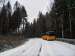 An old orange bus is abandoned on a snowy road in the woods. Winter landscape with frosty road, forest and forgotten vintage bus