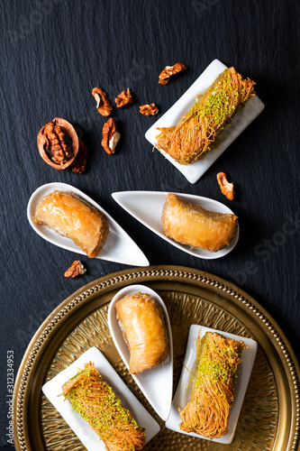 Food concept Oriental arab dessert baklava walnuts and rolled Kanafeh on black s Canvas Print
