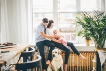 Family With Daugther And Dog Sitting Near The Big Window At The Modern Apartment.