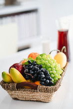 Basket With Fresh Fruit And Juice On White Modern Office Table