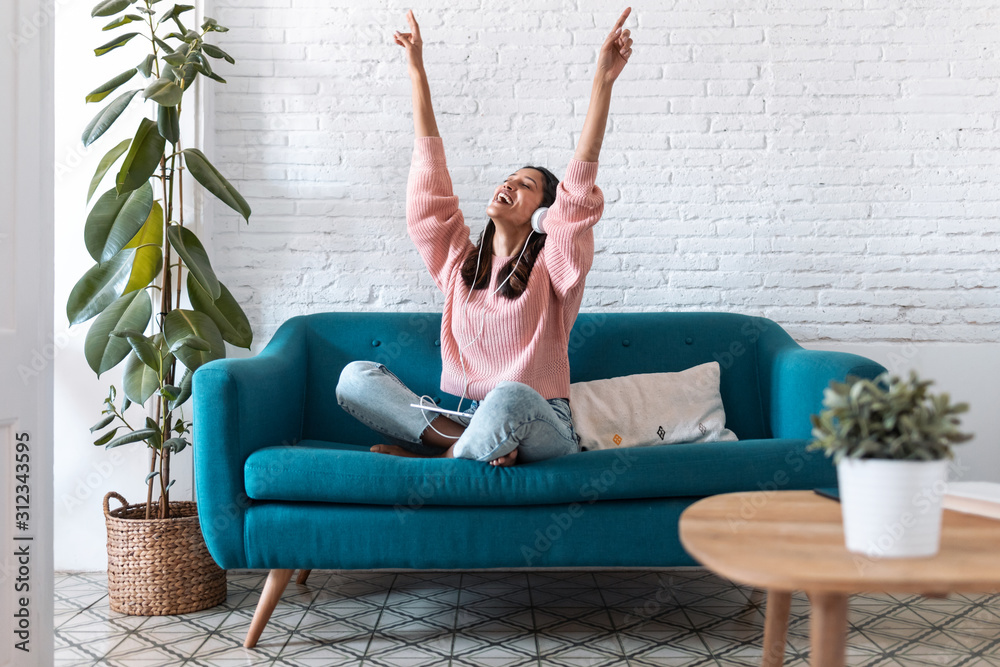 Fototapeta Motivated young woman listening to music with digital tablet while sitting on sofa at home.