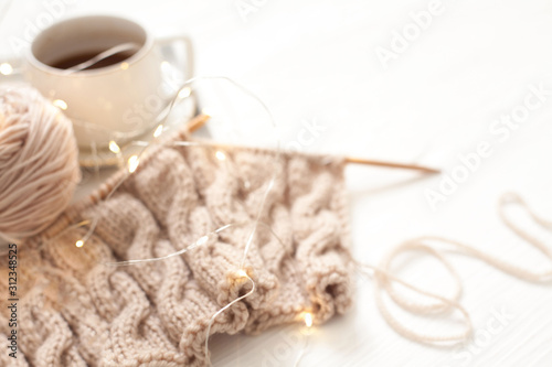 Obraz Cup of coffee and Knitting warm woolen sweater in the winter weekend, top view. - fototapety do salonu