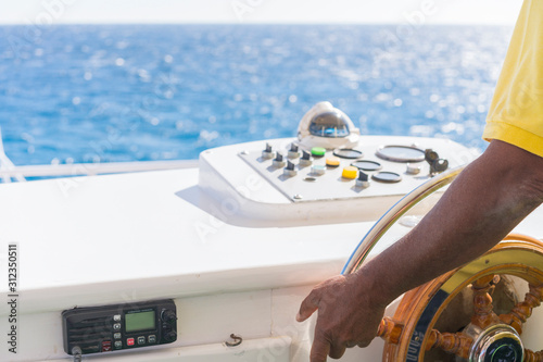 Fotografía  Hand of captain on steering wheel of motor boat in the blue ocean during the fishery day