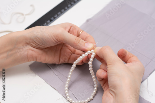 In women's hands jewelry. Bracelet made of white pearls. Canvas Print