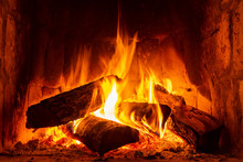 Fire In A Fireplace With Logs And Flames Creating A Sense Of Warmth And Coziness.