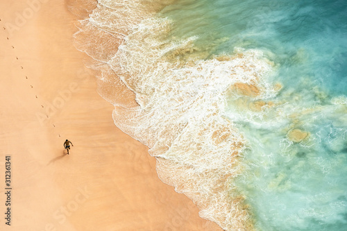 View from above, stunning aerial view of a person running on a beautiful beach bathed by a turquoise sea during sunset Canvas-taulu