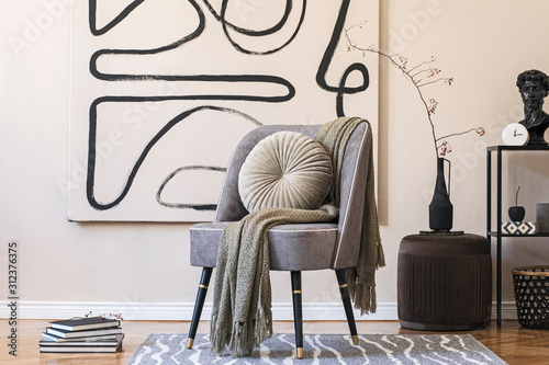 Photo Interior design of living room with stylish gray armchair, abstract paintings on the wall, flowers in vase, pillow, plaid and elegant personal accessories
