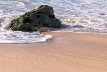 A Wave Wraps Around A Piece Of...