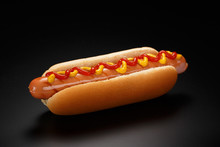 Classic Hot Dog With Ketchup And Mustard On A Black Background.