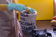 Person with apron and gloves composting in a kitchen