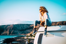 Travel Concept With Independent People Enjoyig The Outdoor Leisure Activity And Wanderlust Life Lifestyle - Woman Sit Down On The Roof Of A Old Nice Vintage Camper Van