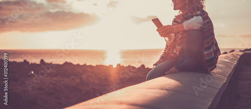 Obraz Trendy woman enjoying the phone connection during a coloured beautiful sunset on the coast - outdoor leisure activity for traveler modern people - fototapety do salonu