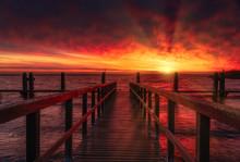 Wooden Pier At Sunrise On Sea
