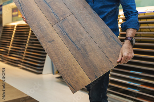 Obraz flooring store salesman with laminate floor sample panel in hands - fototapety do salonu