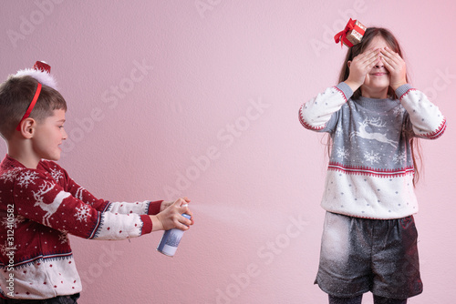 Girl in grey santa sweater and hat closed her eyes with her hands, little boy in Tapéta, Fotótapéta