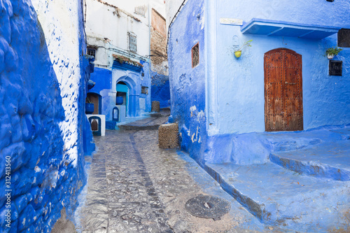 traditional-typical-moroccan-architectural-details-in-chefchaouen-morocco-africa-beautiful-street-of-blue-medina-with-blue-walls-and-decorated-with-various-objects-pots-jugs-a-city-with-narrow