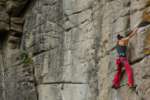 Photo A young woman with a rope engaged in the sports of rock climbing on the rock