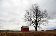 A Small Red Barn Sits Next To...