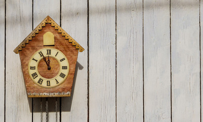 Old clock on a wooden light wall. Vintage clock. Cuckoo clock. Copy-space.