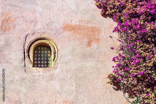 Carta da parati Window in a stucco wall with a Bougainvillea