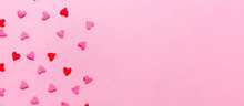 Two Tone Heart Sprinkles On The Solid Pink Background. Romance, Love, Valentines And Mother's Day Concept. Flat Lay, Horizontal Wide Screen Banner Format With Place For Text