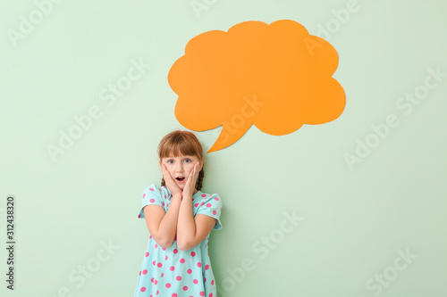 Fotografiet  Surprised little girl with blank speech bubble on color background