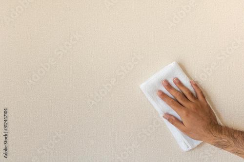 Photo タオルで壁を拭き掃除している男の手