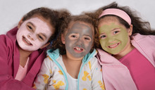 Smiling, Mixed Race Sisters In Bathrobes And Pink, Gray And Green Facial Masks