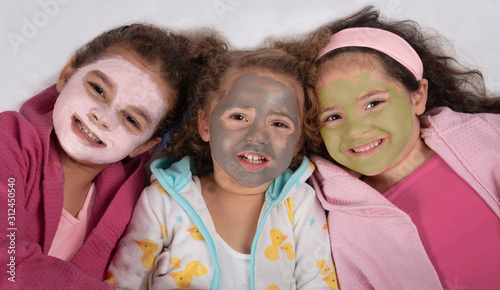 Obraz na plátně Smiling, mixed race sisters in bathrobes and pink, gray and green facial masks