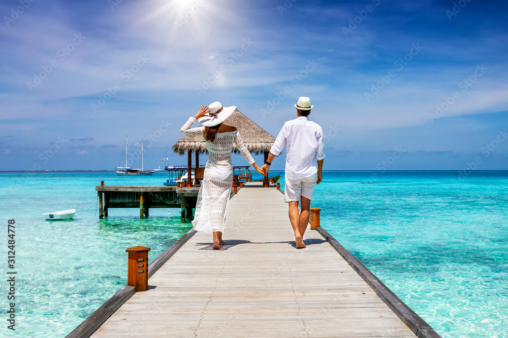 Fototapeta A happy couple in white summer clothing on vacation walks along a wooden pier over tropical, turquoise ocean in the Maldives, Indian Ocean