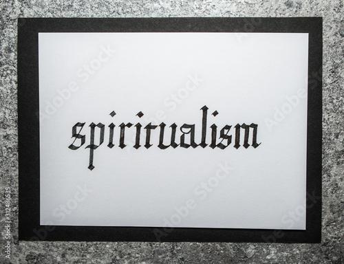Fototapeta Handwritten word Spiritualism. Gothic script calligraphy.