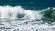 A Blue Sea Wave Hitting The Shore During A Small Storm
