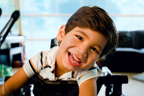 Obraz Happy smiling biracial disabled little boy standing in walker - fototapety do salonu