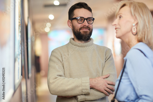 Foto  Waist up portrait of smiling bearded man looking at wife while enjoying exhibiti