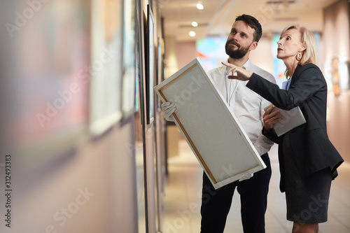 Photo Portrait of elegant mature woman buying painting in art gallery or museum, copy