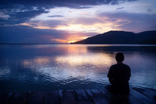 Man Sitting On Dock With Orange Sunset On Purple Blue Sky Along Lake Itza, El Remate, Peten, Guatemala
