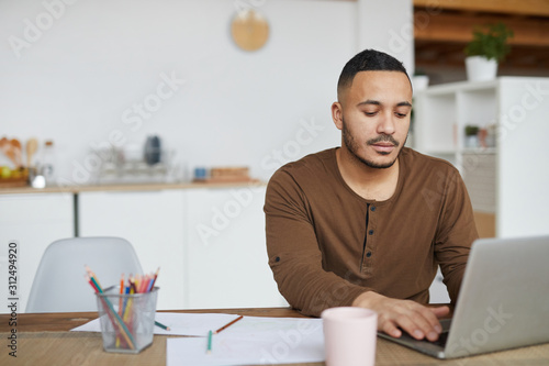Obraz Portrait of modern mixed race man using laptop while working in home interior, copy space - fototapety do salonu