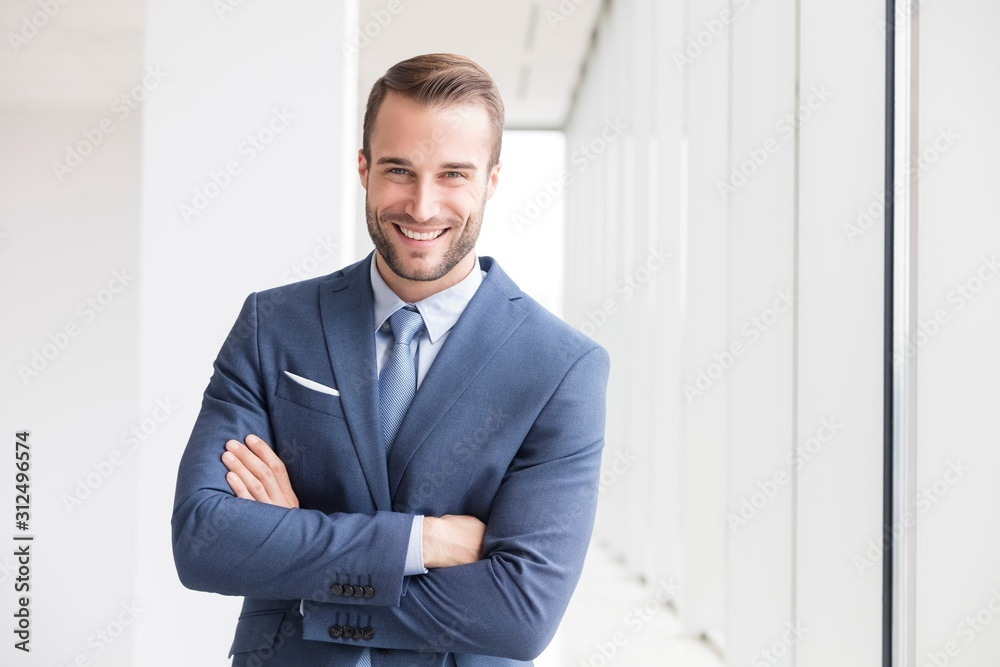 Fototapeta Portrait of smiling handsome young businessman standing with arms crossed in new office