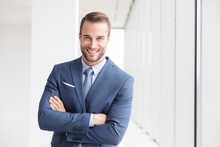 Portrait Of Smiling Handsome Young Businessman Standing With Arms Crossed In New Office