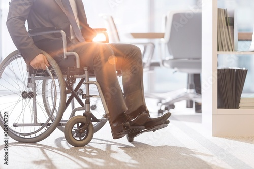 Obraz Low angle view of disabled businessman on wheelchair at modern office - fototapety do salonu