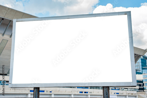 Obraz Advertising billboard mockup in front of modern office buildings - fototapety do salonu