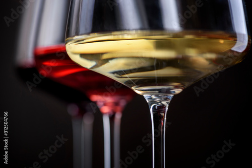 Fototapeta Three glass of red, rose and white wine over black background