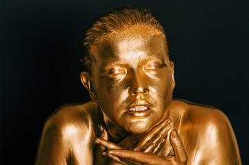 Portrait of sensual woman covered with golden paint, posing on black background, eyes closed