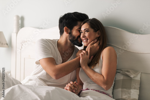 Affectionate young couple relaxing in bed and having a romantic moment Canvas Print