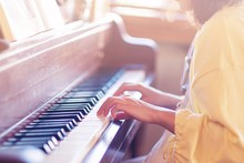 A Woman Playing Piano In Her R...