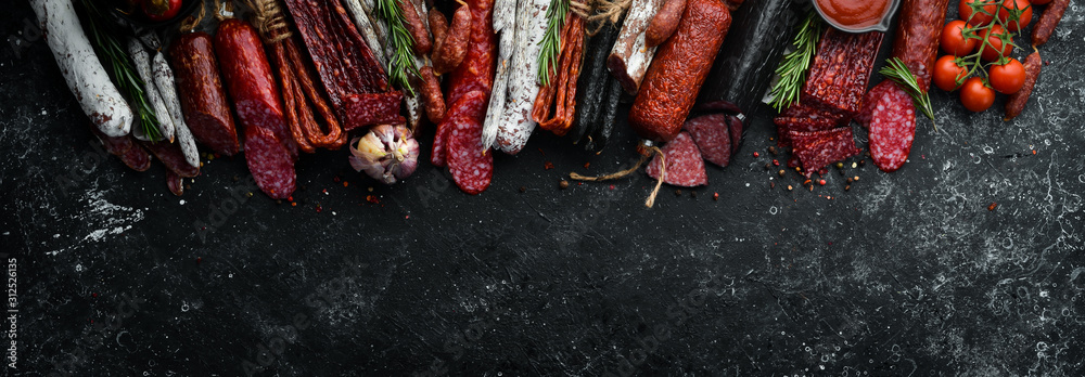 Fototapeta Background of salami, sausages and meat products, on black stone background. Top view. Free space for your text.