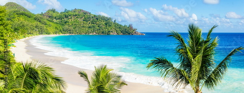 Fototapeta Panoramic view of sandy lonely beach with clear blue water and palm trees , Seyc
